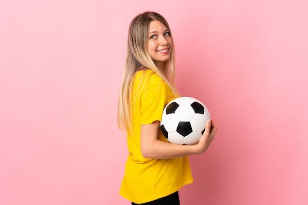 Mulher jovem jogador de futebol isolada na parede rosa rindo