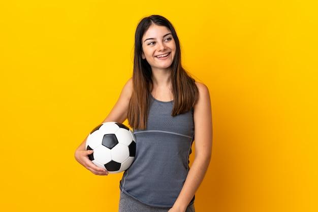 Mulher jovem jogador de futebol isolada na risada amarela