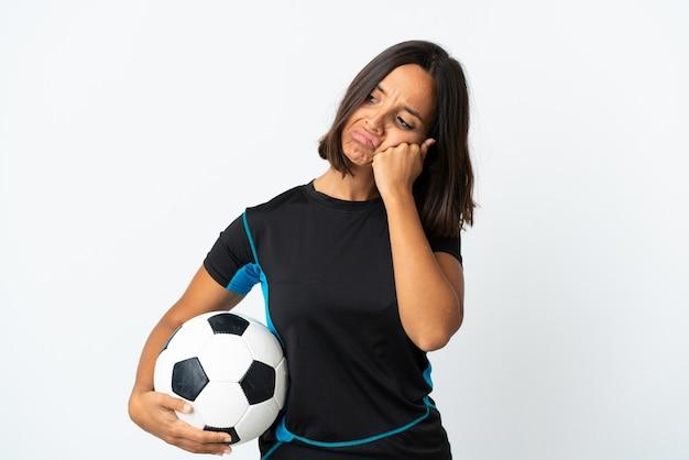 Mulher jovem jogador de futebol isolada no branco com uma expressão cansada e entediada