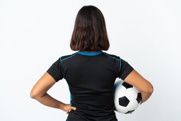 Mulher jovem jogador de futebol isolada no branco na posição traseira