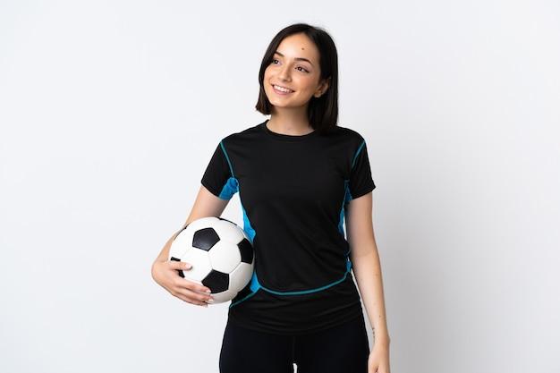 Mulher jovem jogador de futebol isolada no branco pensando em uma ideia enquanto olha para cima