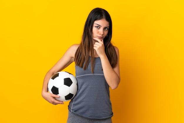 Mulher jovem jogador de futebol isolada no pensamento amarelo