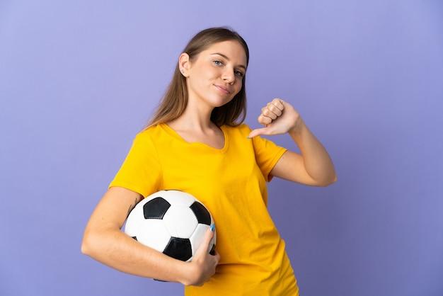 Mulher jovem jogador de futebol lituano isolada em fundo roxo orgulhosa e satisfeita
