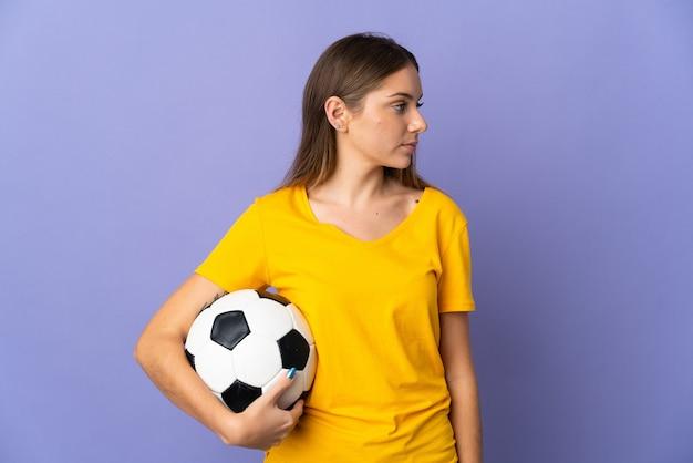Mulher jovem jogador de futebol lituano isolada em um fundo roxo, olhando para o lado