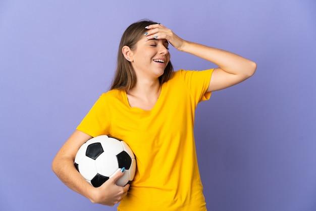 Mulher jovem jogador de futebol lituano isolada em um fundo roxo sorrindo muito