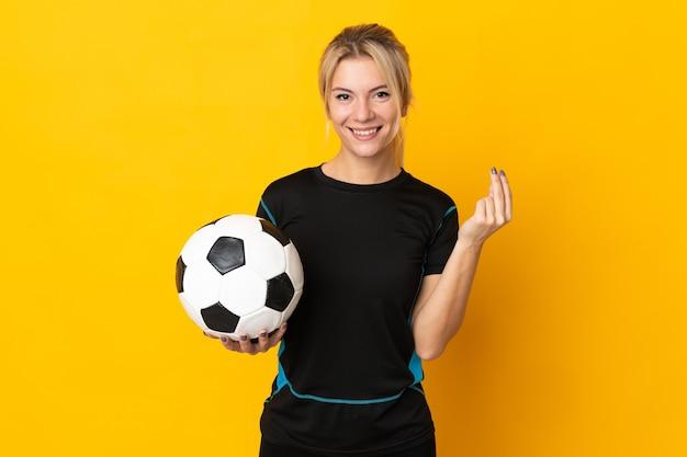 Mulher jovem jogador de futebol russo isolada em fundo amarelo fazendo gesto de dinheiro