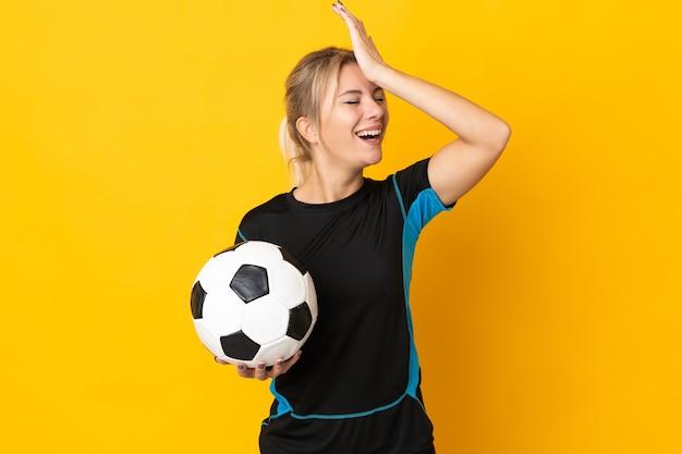 Mulher jovem jogador de futebol russo isolada em fundo amarelo percebeu algo e tem a intenção de encontrar a solução
