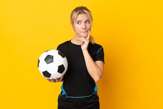Mulher jovem jogador de futebol russo isolada em fundo amarelo, tendo dúvidas e pensando