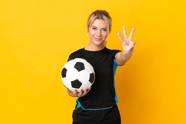 Mulher jovem jogador de futebol russo isolada em um fundo amarelo feliz e contando três com os dedos