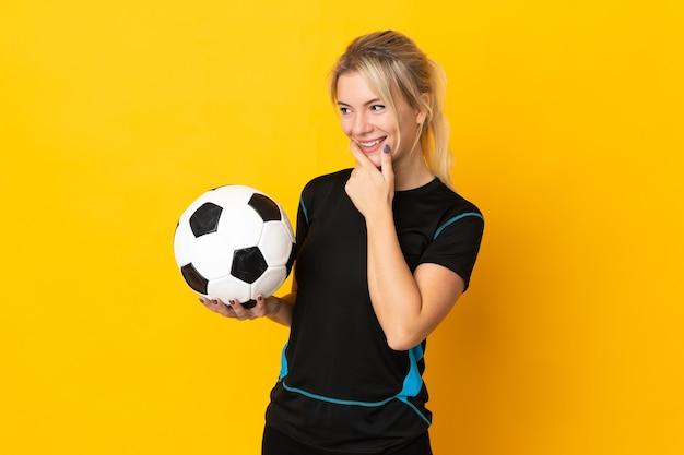 Mulher jovem jogador de futebol russo isolada em um fundo amarelo, olhando para o lado e sorrindo