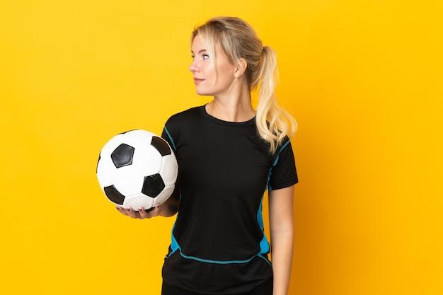 Mulher jovem jogador de futebol russo isolada em um fundo amarelo, olhando para o lado