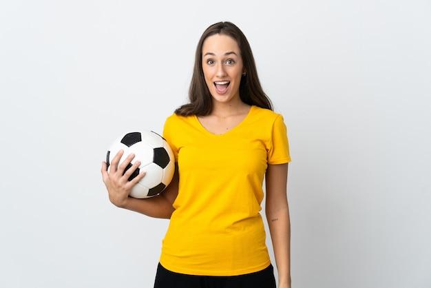 Mulher jovem jogador de futebol sobre fundo branco isolado com expressão facial surpresa