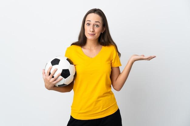 Mulher jovem jogador de futebol sobre fundo branco isolado, tendo dúvidas ao levantar as mãos