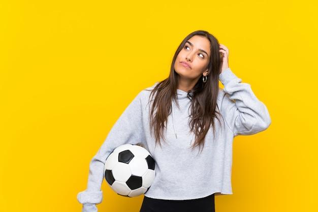 Mulher jovem jogador de futebol sobre parede amarela isolada, tendo dúvidas e com a expressão do rosto confuso