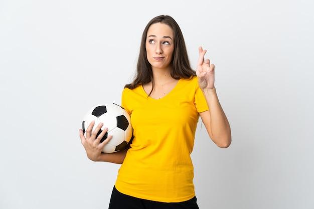 Mulher jovem jogador de futebol sobre um fundo branco isolado com os dedos se cruzando e desejando o melhor