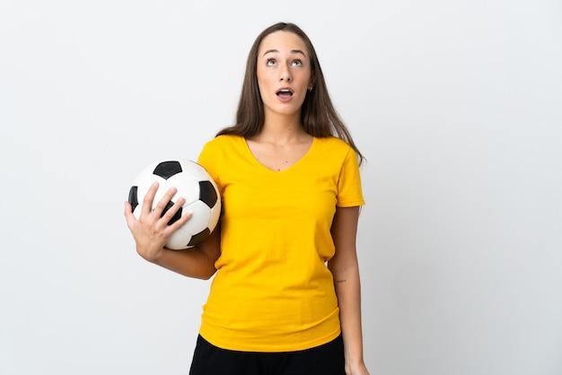 Mulher jovem jogador de futebol sobre uma parede branca isolada olhando para cima e com expressão de surpresa