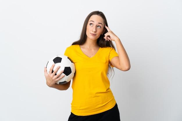 Mulher jovem jogador de futebol sobre uma parede branca isolada, tendo dúvidas e pensando