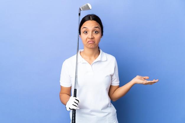 Mulher jovem jogador de golfe ao longo da parede colorida com dúvidas ao levantar as mãos