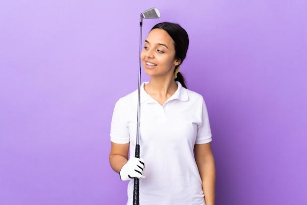 Mulher jovem jogador de golfe ao longo da parede colorida, olhando para o lado