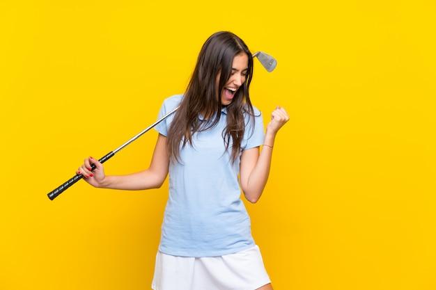 Mulher jovem jogador de golfe isolado muro amarelo comemorando uma vitória
