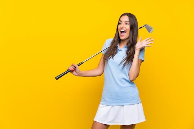Mulher jovem jogador de golfe isolado parede amarela com expressão facial de surpresa