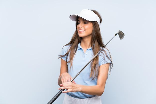 Mulher jovem jogador de golfe isolado parede azul sorrindo muito