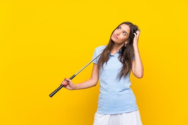 Mulher jovem jogador de golfe sobre parede amarela isolada, tendo dúvidas e com a expressão do rosto confuso