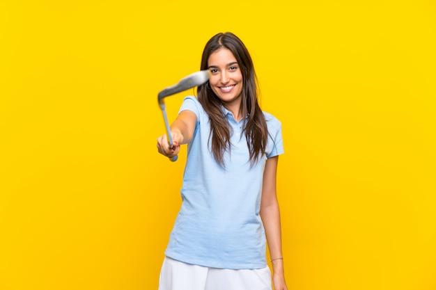 Mulher jovem jogador de golfe sobre parede amarela isolada