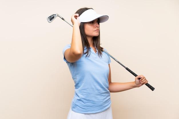 Mulher jovem jogador de golfe sobre parede isolada, tendo dúvidas e com a expressão do rosto confuso