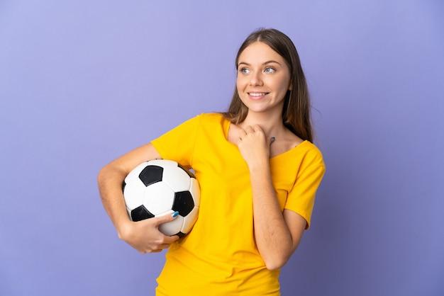 Mulher jovem jogadora de futebol lituana isolada em um fundo roxo, olhando para cima enquanto sorri