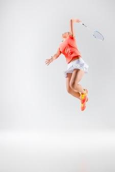 Mulher jovem jogando badminton em uma parede branca