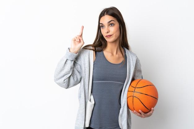 Mulher jovem jogando basquete em branco com os dedos cruzados e desejando o melhor