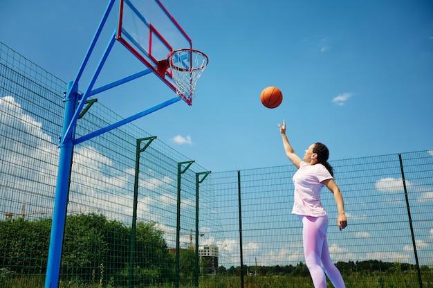 Mulher jovem jogando basquete na quadra e jogando a bola no aro. movimento, conceitos de estilos de vida ativos.