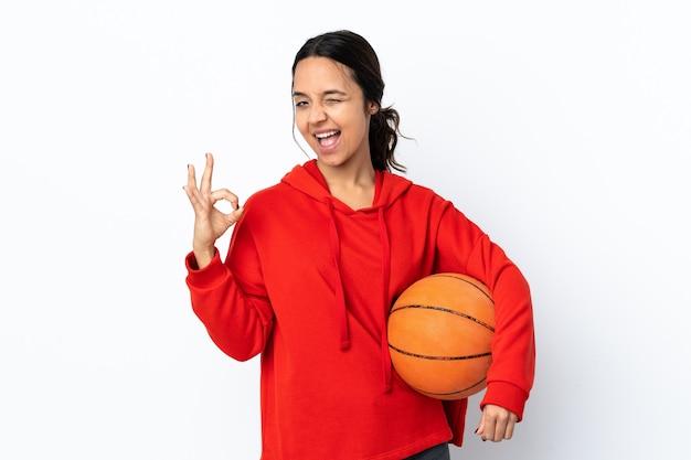 Mulher jovem jogando basquete sobre fundo branco isolado, mostrando sinal de ok com os dedos