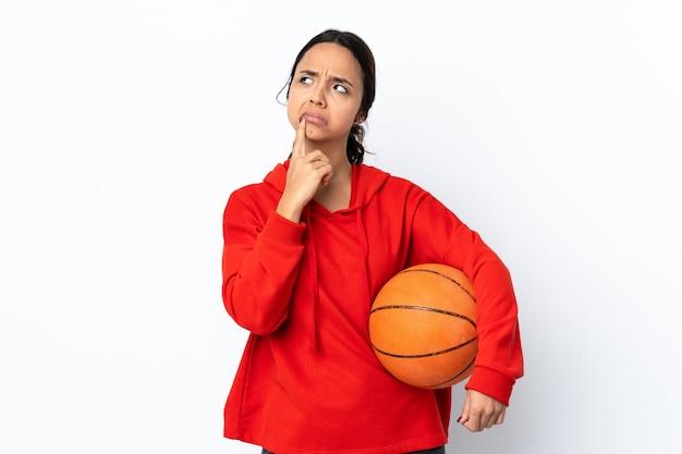 Mulher jovem jogando basquete sobre fundo branco isolado tendo dúvidas enquanto olha para cima