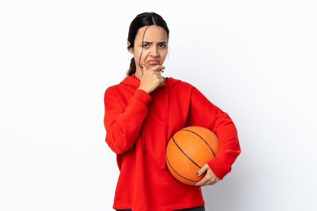 Mulher jovem jogando basquete sobre fundo branco isolado tendo dúvidas