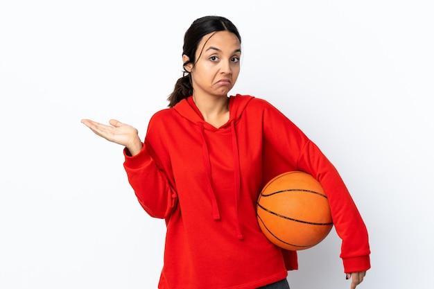 Mulher jovem jogando basquete sobre um branco isolado fazendo um gesto de dúvida