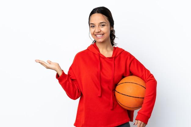 Mulher jovem jogando basquete sobre um fundo branco isolado segurando copyspace imaginário na palma da mão para inserir um anúncio