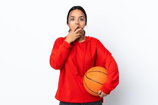 Mulher jovem jogando basquete sobre um fundo branco isolado surpresa e chocada ao olhar para a direita