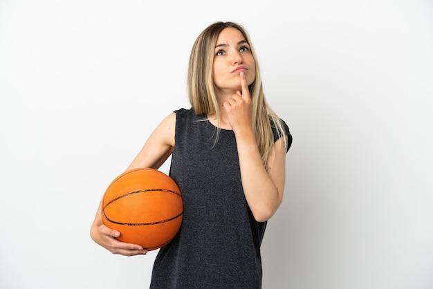 Mulher jovem jogando basquete sobre uma parede branca isolada, tendo dúvidas enquanto olha para cima