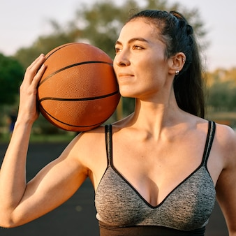 Mulher jovem jogando basquete sozinha