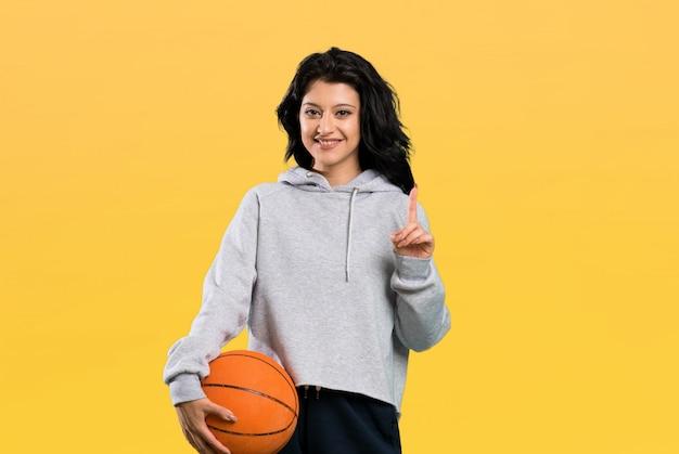 Mulher jovem, jogando basquetebol, apontar cima, um, grande idéia