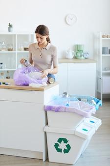 Mulher jovem jogando fora o lixo das sacolas na lixeira da cozinha doméstica de casa