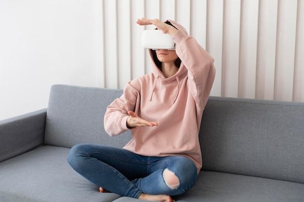 Mulher jovem jogando videogame usando óculos de realidade virtual