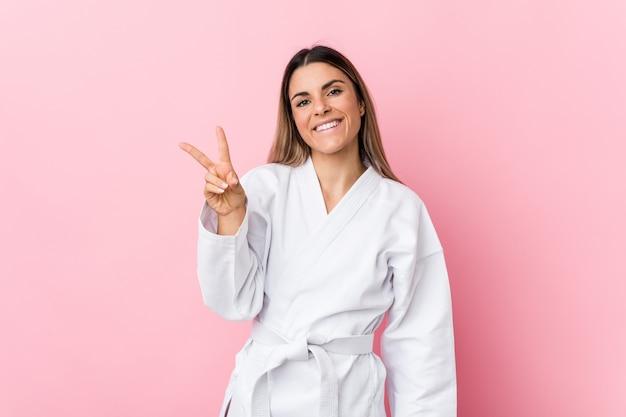 Mulher jovem karatê alegre e despreocupada, mostrando um símbolo de paz com os dedos.