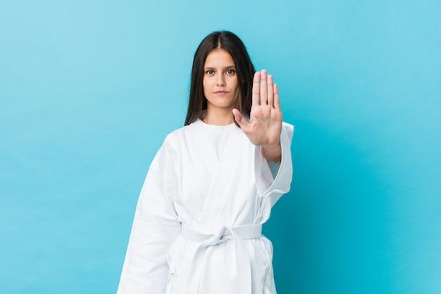 Mulher jovem karatê em pé com a mão estendida, mostrando o sinal de stop, impedindo-o.