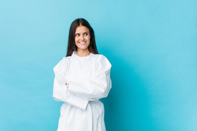 Mulher jovem karatê sorrindo confiante com braços cruzados.