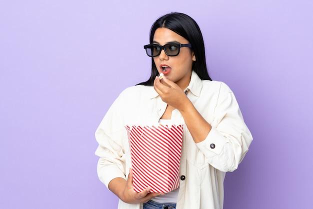 Mulher jovem latina isolada no branco com óculos 3d e segurando um grande balde de pipocas enquanto olha de lado