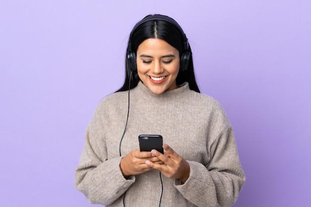 Mulher jovem latina na parede roxa, ouvindo música e olhando para o celular