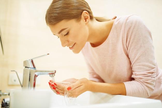Mulher jovem lava o rosto na pia do banheiro.
